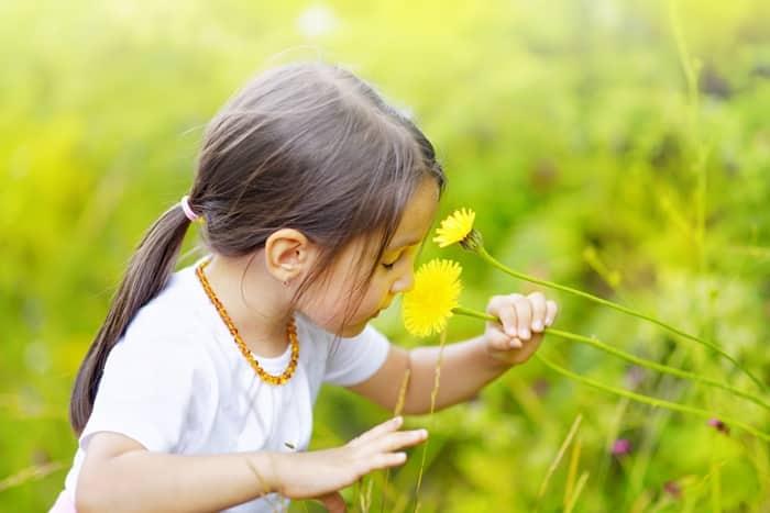 Criança cheirando flor